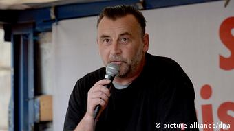 Pegida leader Lutz Bachmann speaking into a microphone