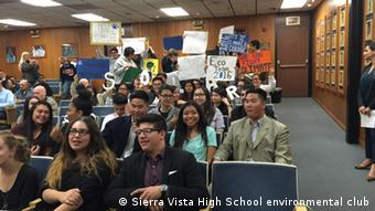 Students hold up pro-environment signs at a school-board meeting