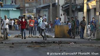 A Kashmiri protester throws a stone at Indian policemen during a protest in Srinagar, Indian controlled Kashmir, Monday, July 18, 2016 (AP Photo/Mukhtar Khan)