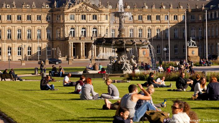 People lounge in the grass in front of Stuttgart's New Palace