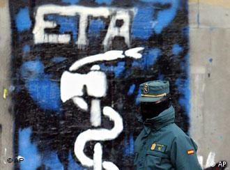 A masked Spanish Civil Guard walks next to a wall painted with graffiti of the Basque separatist group ETA