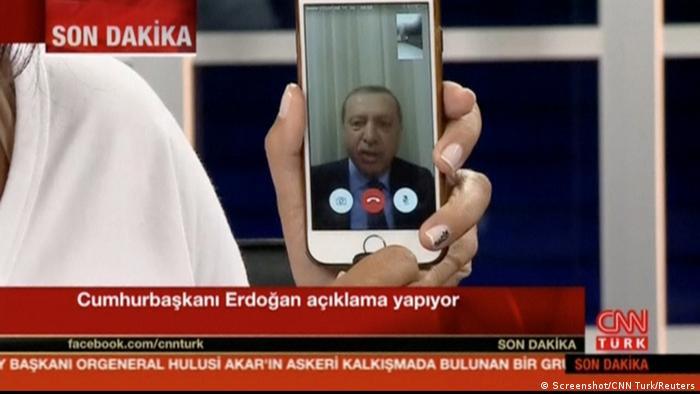 Телеведущий показывает в камеру телефон, с экрана которого Реджеп Тайип Эрдоган обращается к туркам