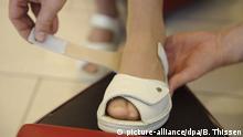 Ein Verkäufer hilft einer Kundin ein Paar weiße Sandalen mit Klettverschluß anzuprobieren, aufgenommen in einem Schuhgeschäft in Soest am 09.04.2009. +++ (C) picture-alliance/dpa/B. Thissen