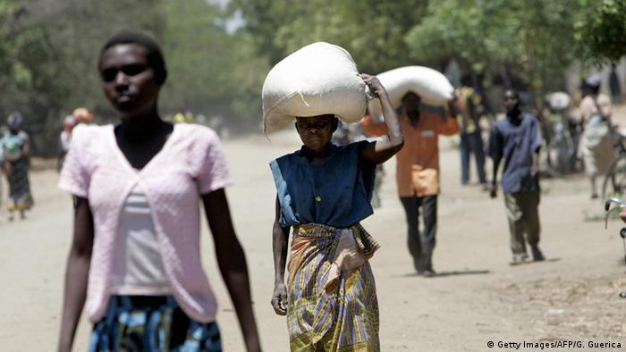 People in Malawi carrying sacks with relief food