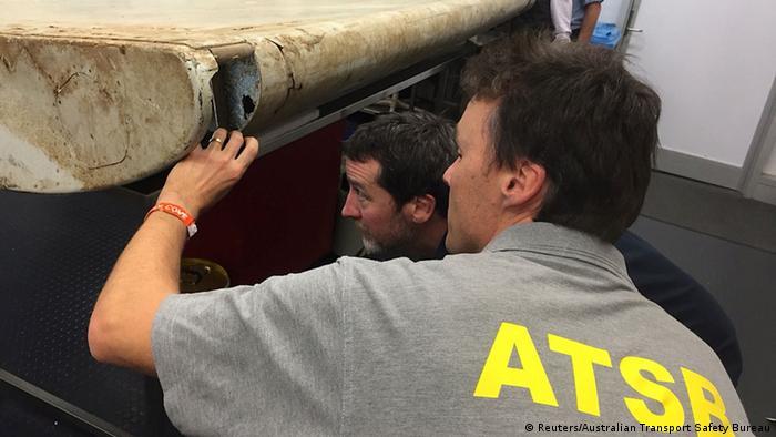 Técnicos de la ATSB examinan un trozo de fuselaje del MH370 localizado en la isla tanzana de Pemba.