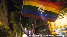 A woman is waving a rainbow flag with the star of david (photo: Omer Messinger)