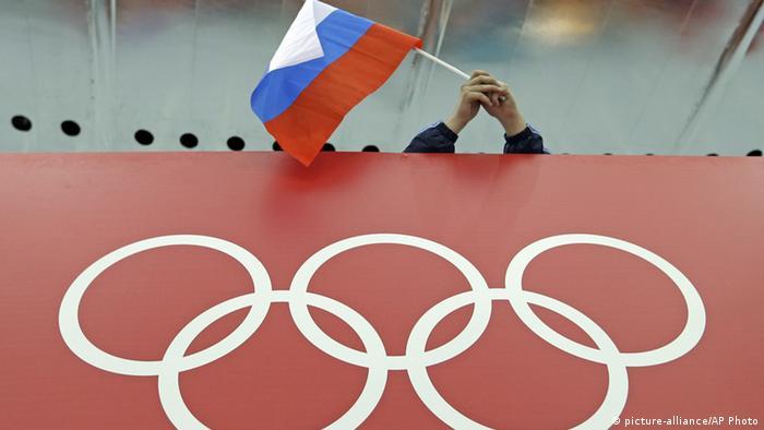 Российский флаг над транспарантом с олимпийскими кольцами
