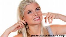Junge Frau leidet unter Lärmbelästigung, hält sich die Ohren zu | Verwendung weltweit picture-alliance/dpa/Chromorange