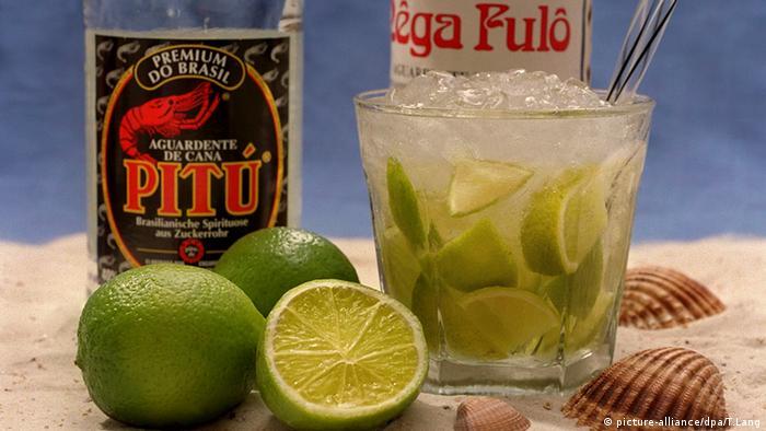 Ein Glas Caipirinha, Limetten und zwei verschiedene Sorten Zuckerrohrschnaps stehen auf einem Tisch . Foto: picture-alliance/dpa/T.Lang