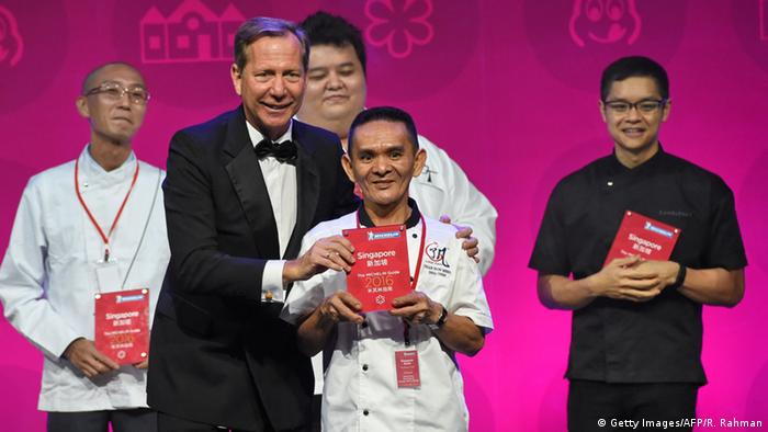 Michael Ellis (CL), international director of the Michelin Guides presents the award for one Michelin star to Chan Han Meng (CR) of Hong Kong Soya Sauce Chicken Rice and Noodle