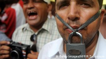 A man with a padlock hanging in front of his mouth at a demonstration by Pakistani journalists in Karachi