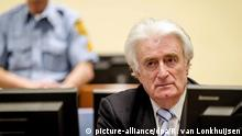 epa05228963 Bosnian Serb wartime leader Radovan Karadzic (R) sits in the courtroom for the reading of his verdict at the International Criminal Tribunal for Former Yugoslavia (ICTY) in The Hague, The Netherlands.The former Bosnian-Serbs leader is indicted for genocide, crimes against humanity, and war crimes. Karadzic is considered the main responsible for the Srebrenica massacre. EPA/ROBIN VAN LONKHUIJSEN   picture-alliance/dpa/R. van Lonkhuijsen