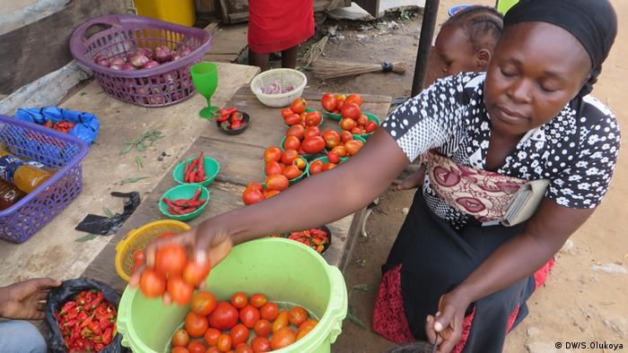 A women holds up a bucket of tomatoes at a market