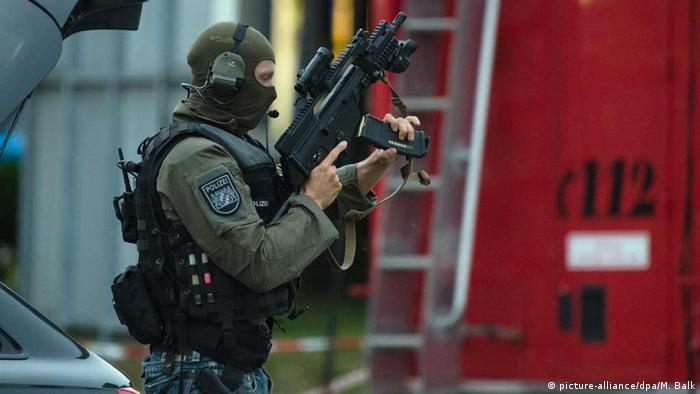 Deutschland Polizist mit Spezialausrüstung steht nahe dem Einkaufszentrum