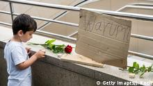 23.07.2016 MUNICH, GERMANY - JULY 23: A small boy places a candle outside the OEZ shopping center the day after a shooting spree left nine victims dead on July 23, 2016 in Munich, Germany. According to police an 18-year-old German man of Iranian descent shot nine people dead and wounded at least 16 before he shot himself in a nearby park. For hours during the spree and the following manhunt the city lay paralyzed as police ordered people to stay off the streets. Original reports of up to three attackers seem to have been unfounded. The shooter's motive is so far unclear. (Photo by Joerg Koch/Getty Images) Copyright: Getty Images/J. Koch