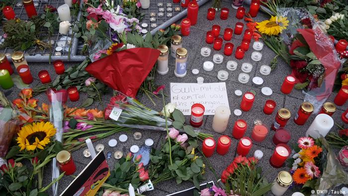 A sign reading Why and flowers for the victims of the July 22, 2016 mass shooting in Munich, Copyright: Reuters/A. Wiegmann