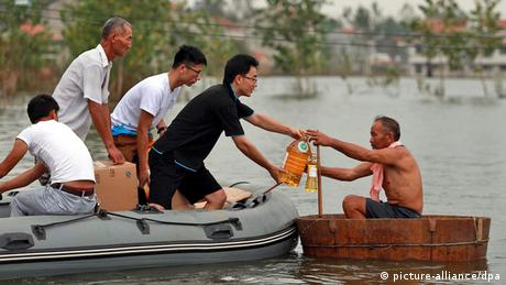 Volunteers giving food supplies to a villager in a makeshift boat on flood water, Xinhua Village of Xinchang county in Wuhan city, Hubei Province of central China on 18 July 2016 (Photo: picture-alliance/dpa)