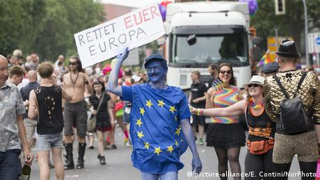 A reveler carries a sign that read: Save your Europe