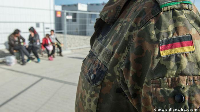 Bundeswehrsoldat steht im Wartezentrum Asyl in Erding vor Flüchtlingen (picture-alliance/dpa/A. Weigel)