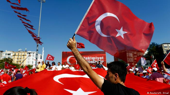 A man waves Turkey's national flag as supporters of various political parties gather in Istanbul's Taksim Square