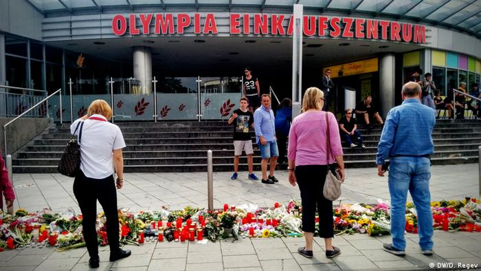 People mourning outside of the Olympia shopping center in Munich, Germany