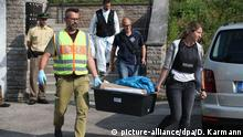 Beamte tragen beschlagnahmtes Material aus einem Flüchtlingsheim in Ansbach