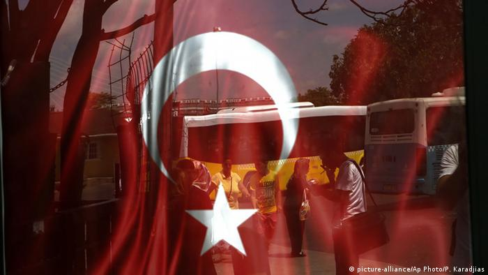 A Turkish flag superimposed over a photo of journalists being arrested