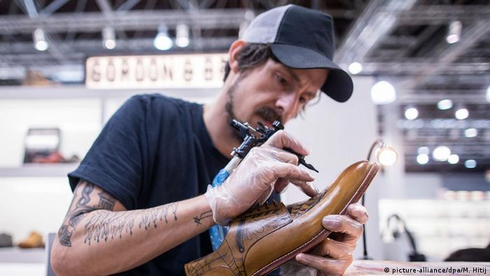 Max Gartenbach tattoos a leather shoe at the GDS shoe fair in Dusseldorf 2016, Copyright: picture-alliance/dpa/M. Hitij