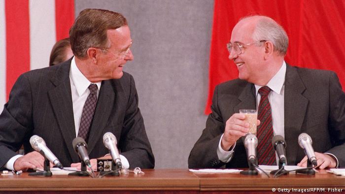 Dois homens de paletó e gravata, sentados, usando óculos, sorriem um para o outro