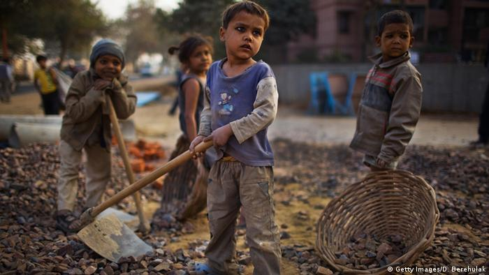 Four children standing on a road by Nehru Stadion in Neu Delhi holding work tools.