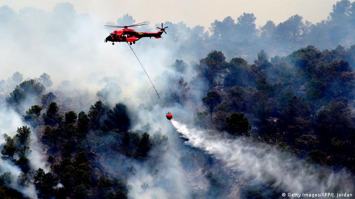 A helicopter drops water on a wildfire burning in Artana, near Castellon, eastern Spain, on July 26, 2016 (Photo: Getty Images/AFP/J. Jordan)