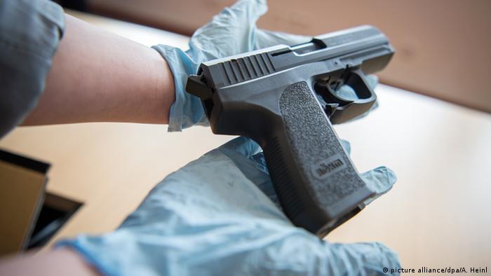 Deutschland Darknet Waffen. Eine BKA Mitarbeiterin präsentiert eine bei einem Darknet-Händler beschlagnahmte Pistole