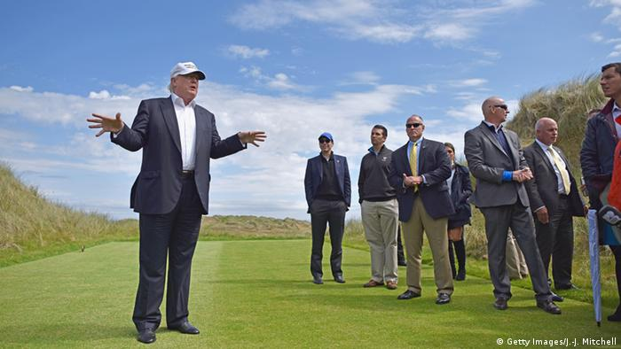 Trump stands on a golf course in Aberdeen