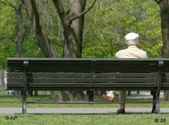 Пожилой человек сидит одиноко на скамейке