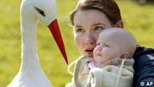 Jutta Roehrig visits a stork with her five-month-old daughter Lea in Essen, 2002