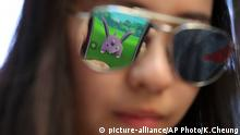 A mobile screen is reflected on a fan's sunglasses as she plays Pokemon Go in Hong Kong, Monday, July 25, 2016. Pokemon fans participated in creatures hunting on Monday as the app was released to both iPhone and Android users. (AP Photo/Kin Cheung) |