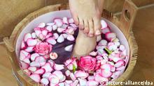 Archiv Frau badet ihre Füße in einer Schüssel mit Rosenblättern | Verwendung weltweit, Keine Weitergabe an Wiederverkäufer. (c) picture-alliance/dpa