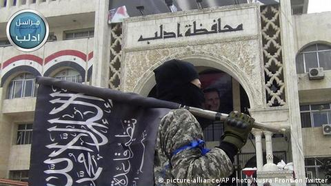 A fighter from Syria's al-Qaida-linked Nusra Front holds his group flag as he stands in front of the governor building in Idlib province