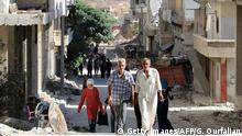 People walk on a street in the neighbourhood of Bani Zeid, on Aleppo's northern outskirts