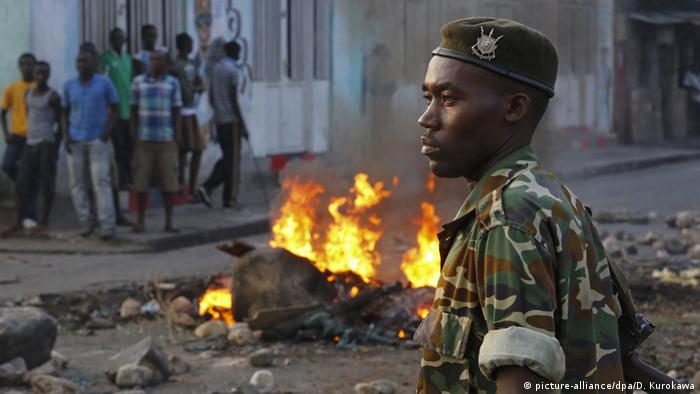 A Burundian soldier looks on in front of a burning barricade while people stand in the background