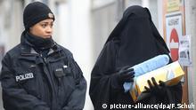 Eine verschleierte Frau im Niqab neben einer Polizistin