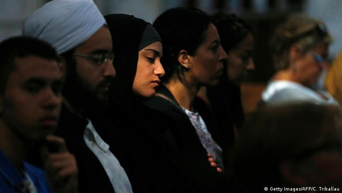 A Muslim woman looks on as people attend a Mass in tribute to priest Jacques Hamel in the Rouen Cathedral (photo: CHARLY TRIBALLEAU/AFP/Getty Images)