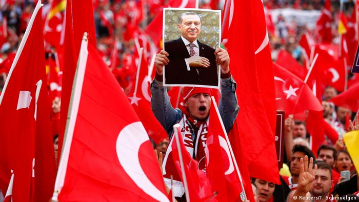 A supporter of the president holds up Erdogan's picture during a rally in Cologne, Germany