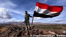 Syrien Soldat der Regierung mit syrischer Flagge (picture alliance/dpa/V. Sharifulin)