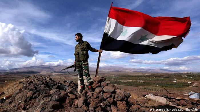 A Syrian government army soldier with a national flag