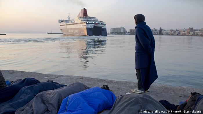 Migrants and refugees sleep as a man from Pakistan wrapped in a blanket watches a ferryboat leaving the port of the Greek island of Chios picture alliance/AP Photo/P. Giannakouris