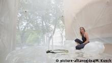 23.07.2016 Die Studentin Franziska sitzt am 23.07.2016 in Bochum (Nordrhein-Westfalen) zwischen Häusern in einer Wohn-Blase. Architekturstudenten in Bochum haben am Freitag ein Experiment zur Zukunft des studentischen Wohnens gestartet. In einer etwa drei Meter schmalen Lücke zwischen zwei Wohnhäusern installieren sie eine Art Blase aus lichtdurchlässigem Kunststoff, die man per Leiter über eine zur Dusche umgebaute Telefonzelle betritt. Copyright: picture-alliance/dpa/M. Kusch