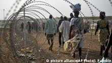 July 25, 2016**** FILE- In this file photo taken Tuesday, Jan. 19, 2016, displaced people walk next to a razor wire fence at the United Nations base in the capital Juba, South Sudan. South Sudanese government soldiers raped dozens of ethnic Nuer women and girls last week just outside a United Nations camp where they had sought protection from renewed fighting, and at least two died from their injuries, witnesses and civilian leaders said. The rapes in the capital of Juba highlighted two persistent problems in the chaotic country engulfed by civil war: targeted ethnic violence and the reluctance by U.N. peacekeepers to protect civilians. (AP Photo/Jason Patinkin, File)   picture alliance/AP Photo/J. Patinkin