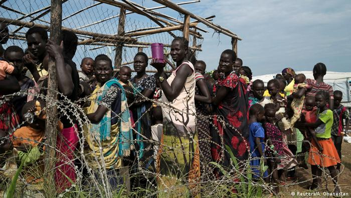 Women and children are queuing behind a barbed-wired fence in a UN camp.