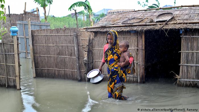 A woman holds her child outside a flooded hut in Bangladesh
